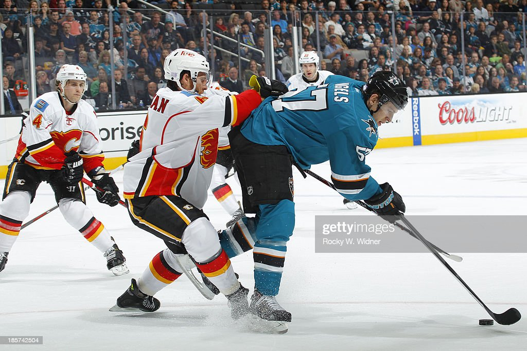 Tommy Wingels #57 of the San Jose Sharks battles with Dennis Wideman #6 of the Calgary Flames for the puck at SAP Center on October 19 2013 in San Jose, California.