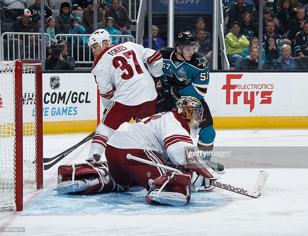 Tommy Wingels #57 of the San Jose Sharks creates traffic in front of the net against Mike Smith #41 and Raffi Torres #37 of the Phoenix Coyotes during an NHL game on February 9, 2013 at HP Pavilion in San Jose, California.