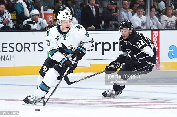 Tommy Wingels of the San Jose Sharks handles the puck against Trevor Lewis of the Los Angeles Kings in the NHL season opener at STAPLES Center on...