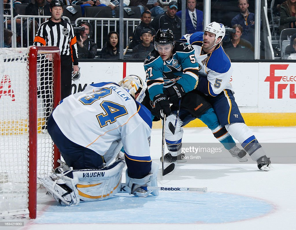 Tommy Wingels #57 of the San Jose Sharks looks for a rebound against Jake Allen #34 and Barret Jackman #5 of the St. Louis Blues during an NHL game on March 9, 2013 at HP Pavilion in San Jose, California.