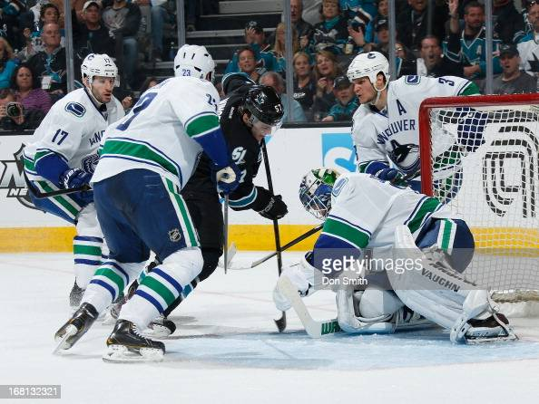 Tommy Wingels of the San Jose Sharks looks for a rebound against Ryan Kesler Alexander Edler Kevin Bieksa and Cory Schneider of the Vancouver Canucks...