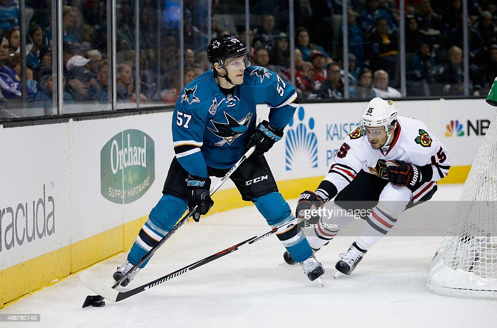 Tommy Wingels #57 of the San Jose Sharks looks to pass the puck while covered by Artem Anisimov #15 of the Chicago Blackhawks at SAP Center on November 25, 2015 in San Jose, California.