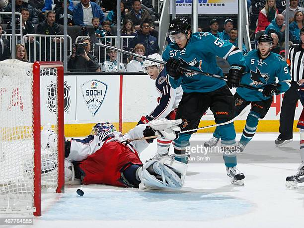 Tommy Wingels of the San Jose Sharks scores a goal against Sergei Bobrovsky and Matt Calvert of the Columbus Blue Jackets during an NHL game on...
