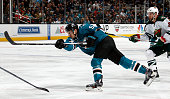 Tommy Wingels of the San Jose Sharks shoots puck against Tyson Strachan of the Minnesota Wild during a NHL game at the SAP Center at San Jose on...