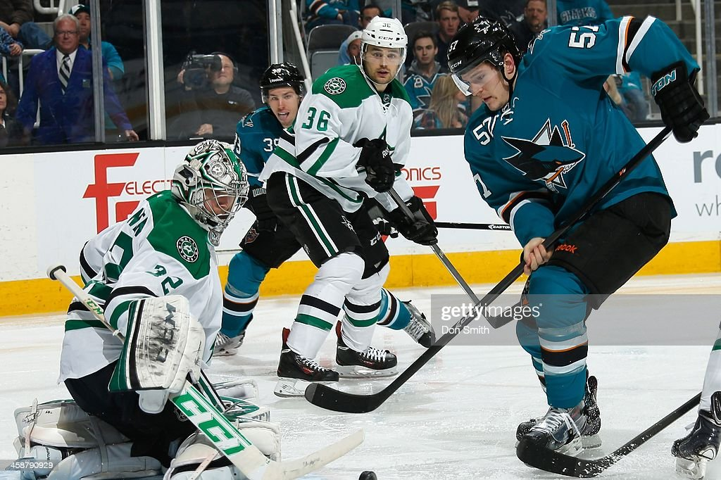 Tommy Wingels #57 of the San Jose Sharks tries to get one into the net against Kari Lehtonen #32 of the Dallas Stars during an NHL game on December 21, 2013 at SAP Center in San Jose, California.