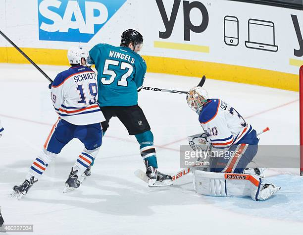 Tommy Wingels of the San Jose Sharks tries to score against goalie Ben Scrivens and Justin Schultz of the Edmonton Oilers during an NHL game on...
