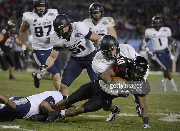 Tommylee Lewis of the Northern Illinois Huskies is tackled by the defense of the Utah State Aggies en route to Aggies 2114 win over the Northern...