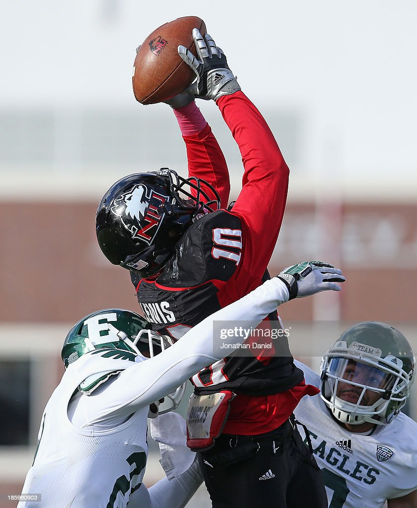 Tommylee Lewis #10 of the Northern Illinois Huskies tries to make a catch as he is hit by Ja'Ron Gillespie #21 (L) and Donald Coleman #3 of the Eastern Michigan Eagles at Brigham Field on October 26, 2013 in DeKalb, Illinois.
