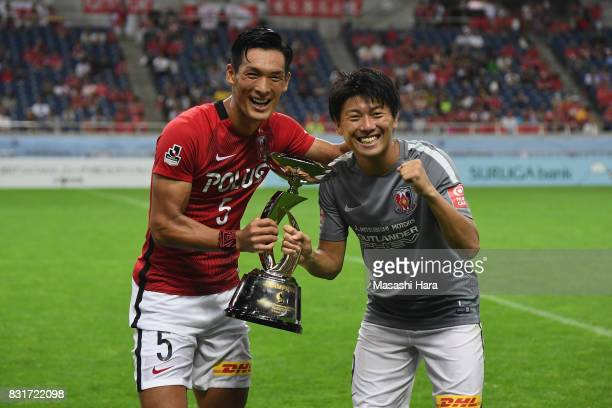 Tomoaki Makino and Yuki Muto of Urawa Red Diamonds celebrate with the trophy after the Suruga Bank Championship match between Urawa Red Diamonds and...