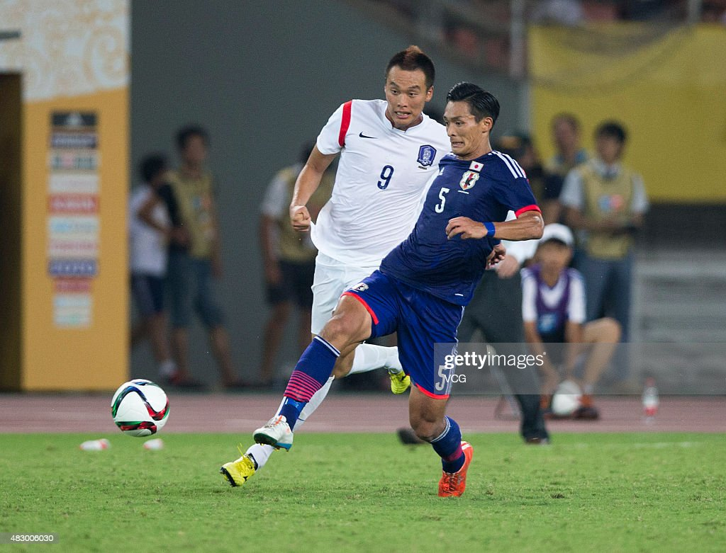 Tomoaki Makino #5 of Japan and Kim Shin-wook #9 of South Korea vie for the ball in group match between Japan and South Korea during EAFF East Asian Cup 2015 at Wuhan Sports Center Stadium on August 5, 2015 in Wuhan, Hubei Province of China.