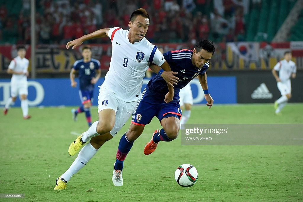 Tomoaki Makino (R) of Japan fights for the ball with Kim Shinwook (L) of South Korea during men's East Asian Cup football match at the Wuhan Sports Center Stadium in Wuhan on August 5, 2015. AFP PHOTO / WANG ZHAO