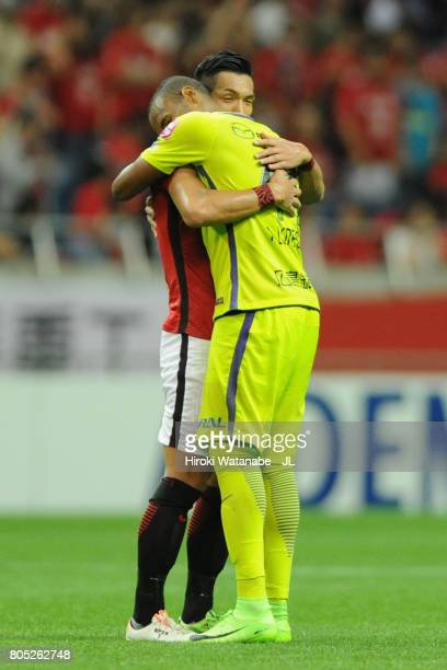 Tomoaki Makino of Urawa Red Diamonds and Anderson Lopes of Sanfrecce Hiroshima embrace each other after the JLeague J1 match between Urawa Red...