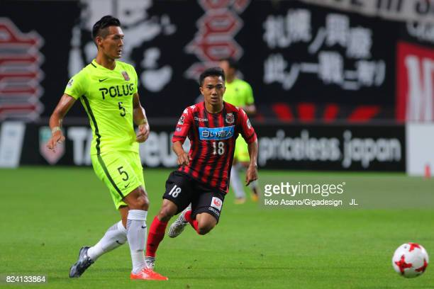 Tomoaki Makino of Urawa Red Diamonds and Chanathip Songkrasin of Consadole Sappporo compete for the ball during the JLeague J1 match between...