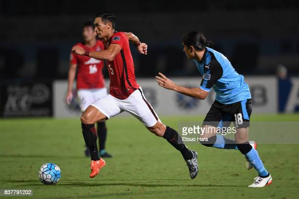 Tomoaki Makino of Urawa Red Diamonds and Elsinho of Kawasaki Frontale compete for the ball during the AFC Champions League quarter final first leg...