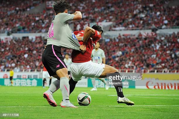 Tomoaki Makino of Urawa Red Diamonds and Kim Min Woo of Sagan Tosu pull shirts each other at referee's blind spot during the JLeague match between...