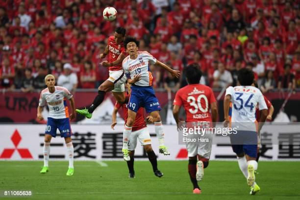 Tomoaki Makino of Urawa Red Diamonds and Kisho Yano of Albirex Niigata compete for the ball during the JLeague J1 match between Urawa Red Diamonds...