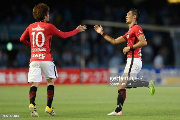 Tomoaki Makino of Urawa Red Diamonds celebrates scoring his side's first goal with his team mate Yosuke Kashiwagi during the JLeague J1 match between...