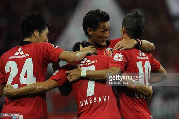 Tomoaki Makino of Urawa Red Diamonds celebrates the second goal by Marcio Richardes with Tsukasa UmesakiGanki Haraguchi during the JLeague match...