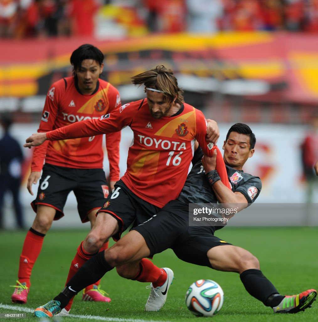 Tomoaki Makino (R) of Urawa Red Diamonds challenges Kennedy of Nagoya Grampus during the J. League match between Nagoya Grampus and Urawa Red Diamonds at the Toyota Stadium on April 12, 2014 in Toyota, Japan.