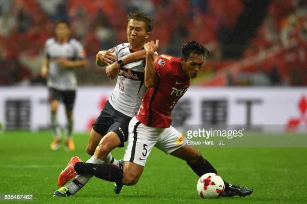 Tomoaki Makino of Urawa Red Diamonds controls the ball under pressure of Kensuke Nagai of FC Tokyo during the JLeague J1 match between Urawa Red...