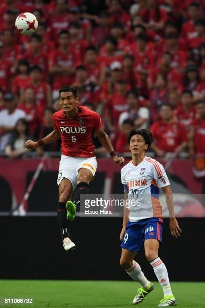 Tomoaki Makino of Urawa Red Diamonds heads the ball in front of Kisho Yano of Albirex Niigata during the JLeague J1 match between Urawa Red Diamonds...
