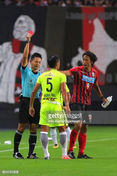 Tomoaki Makino of Urawa Red Diamonds is shown a red card by referee Ryuji Sato during the JLeague J1 match between Consadole Sapporo and Urawa Red...