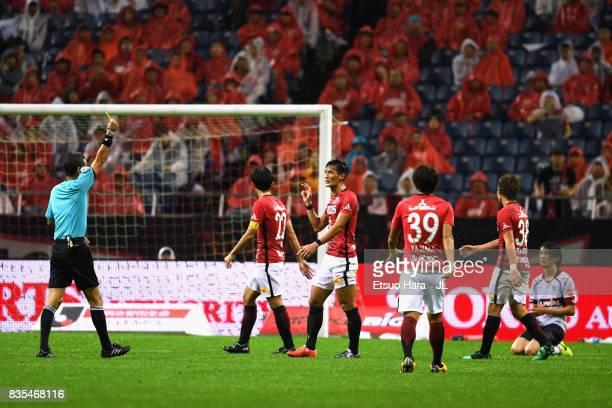 Tomoaki Makino of Urawa Red Diamonds is shown a yellow card by referee Itaru Hirose during the JLeague J1 match between Urawa Red Diamonds and FC...