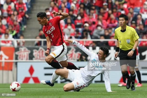 Tomoaki Makino of Urawa Red Diamonds is tackled by Takuma Arano of Consadole Sapporo during the JLeague J1 match between Urawa Red Diamonds and...