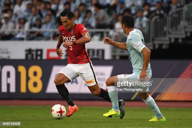 Tomoaki Makino of Urawa Red Diamonds takes on Fozil Musaev of Jubilo Iwata during the JLeague J1 match between Jubilo Iwata and Urawa Red Diamonds at...
