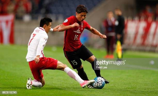 Tomoaki of Urawa Red Diamonds challenged by Wu Lei of Shanghai SIPG during the AFC Champions League semi final second leg match between Urawa Red...