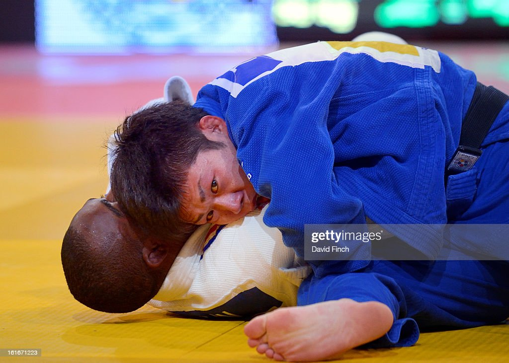 Tomofumi Takajo of Japan (blue) held <a gi-track='captionPersonalityLinkClicked' href=/galleries/search?phrase=Dimitri+Dragin&family=editorial&specificpeople=2568994 ng-click='$event.stopPropagation()'>Dimitri Dragin</a> of France for ippon (10 points) to win the u66kgs bronze medal during the Paris Grand Slam on day 1, Saturday, February 09, 2013 at the Palais Omnisports de Paris, Bercy, Paris, France.