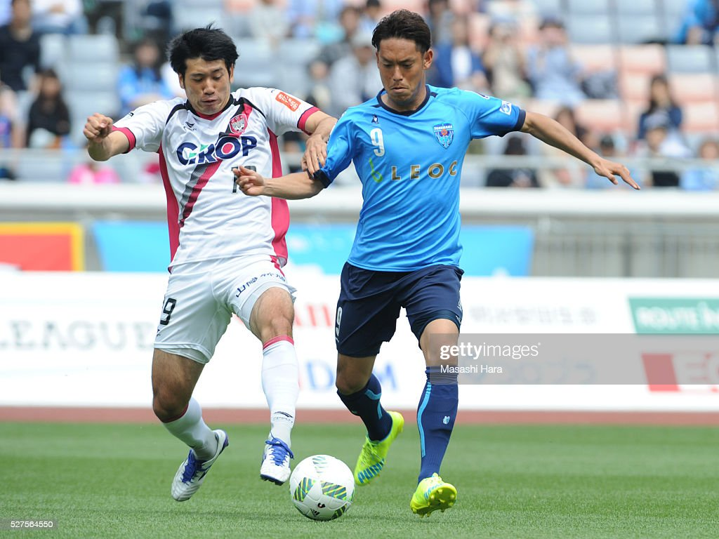 Tomohiro Tsuda #9 of Yokohama FC (R) and Eiichi Katayama #19 of Fagiano Okayama compete for the ball during the J.League second division match between Yokohama FC and Fagiano Okayama at the Nissan Stadium on May 3, 2016 in Yokohama, Kanagawa, Japan.
