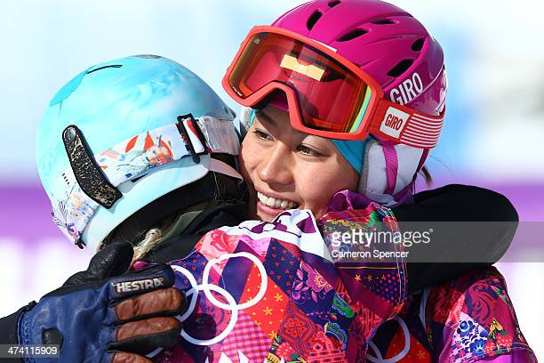 Tomoka Takeuchi of Japan hugs Julie Zogg of Switzerland in the Snowboard Ladies' Parallel Slalom 1/8 Finals on day 15 of the 2014 Winter Olympics at...
