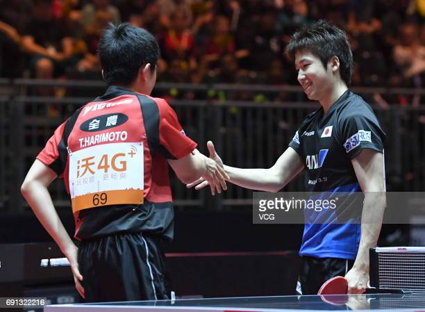 Tomokazu Harimoto of Japan shakes hands with Jun Mizutani of Japan during Men's Singles second round match on day 4 of World Table Tennis...