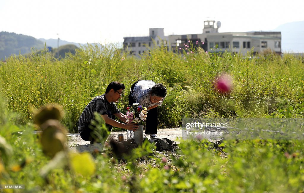 Tomoko Ito (R), 76, and her son Shigehiro offer a flower bunch to the place where her house used to stand and lost her husbund Katsuichiro by March 11 tsunami last year on September 11, 2012 in Otsuchi, Iwate, Japan. She held the funeral for his husband in May this year though he is still missing. 18 months on, still 2,814 people are missing and 340,000 people are forced to live at temporary housing.