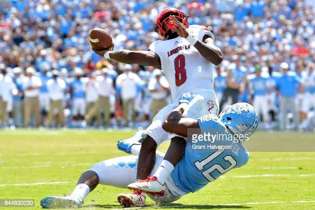 Tomon Fox of the North Carolina Tar Heels pressures Lamar Jackson of the Louisville Cardinals during the game at Kenan Stadium on September 9 2017 in...