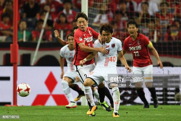 Tomoya Ugajin of Urawa Red Diamonds and Akimi Barada of Omiya Ardija compete for the ball during the JLeague J1 match between Urawa Red Diamonds and...