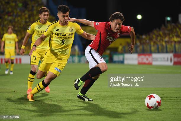 Tomoya Ugajin of Urawa Red Diamonds and Cristiano of Kashiwa Reysol compete for the ball during the JLeague J1 match between Kashiwa Reysol and Urawa...