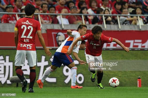 Tomoya Ugajin of Urawa Red Diamonds and Kei Koizumi of Albirex Niigata compete for the ball during the JLeague J1 match between Urawa Red Diamonds...