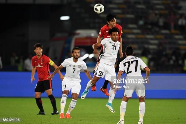 Tomoya Ugajin of Urawa Red Diamonds and Romarinho of Al Jazira compete for the ball during the FIFA Club World Cup match between Al Jazira and Urawa...