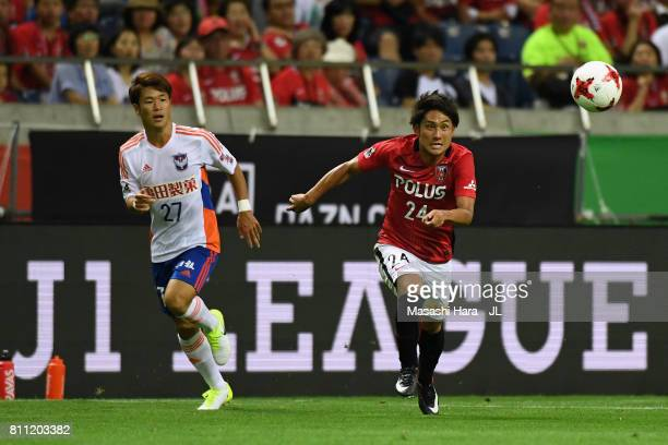 Tomoya Ugajin of Urawa Red Diamonds and Yuto Horigome of Albirex Niigata compete for the ball during the JLeague J1 match between Urawa Red Diamonds...