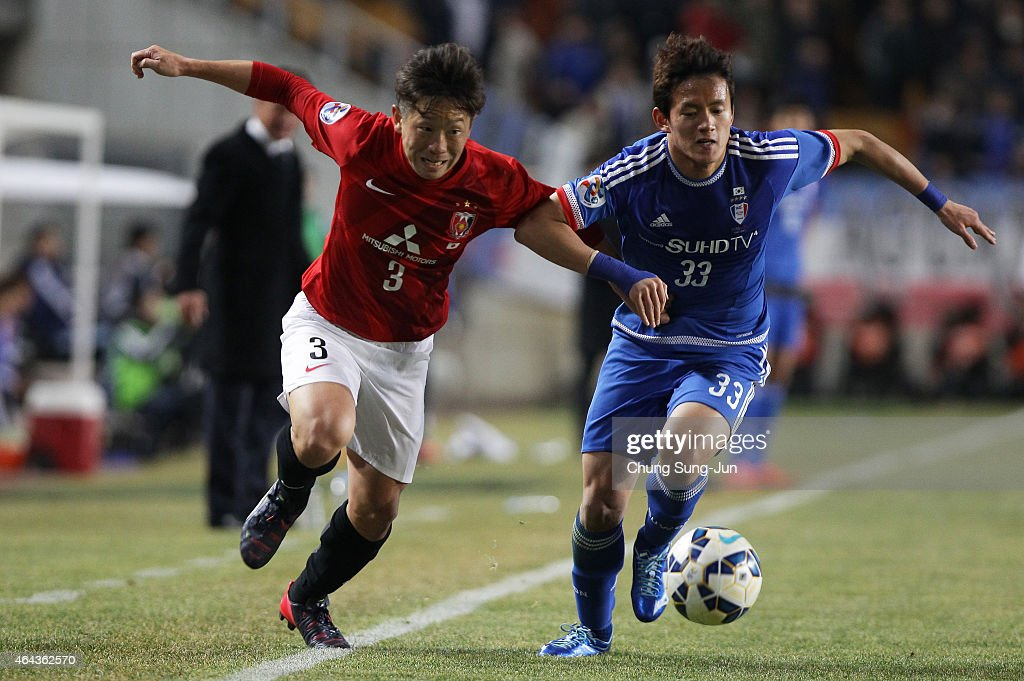 Tomoya Ugajin of Urawa Red Diamonds compete for the ball with Hong Chul of Suwon Samsung FC during the AFC Champions League Group G match between...