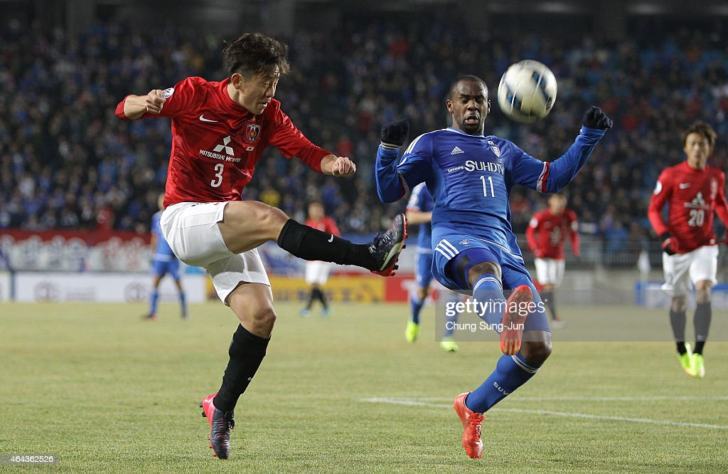 Tomoya Ugajin of Urawa Red Diamonds compete for the ball with Leonardo Marins of Suwon Samsung FC during the AFC Champions League Group G match...