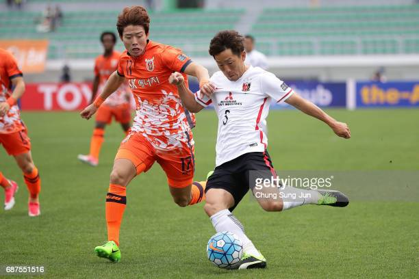 Tomoya Ugajin of Urawa Red Diamonds competes for the ball with Ahn HyunBeom of Jeju United FC during the AFC Champions League Round of 16 match...