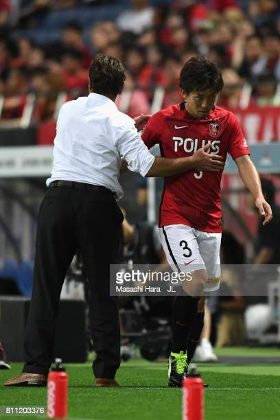 Tomoya Ugajin of Urawa Red Diamonds is embraced by head coach Mihailo Petrovic after substituted during the JLeague J1 match between Urawa Red...