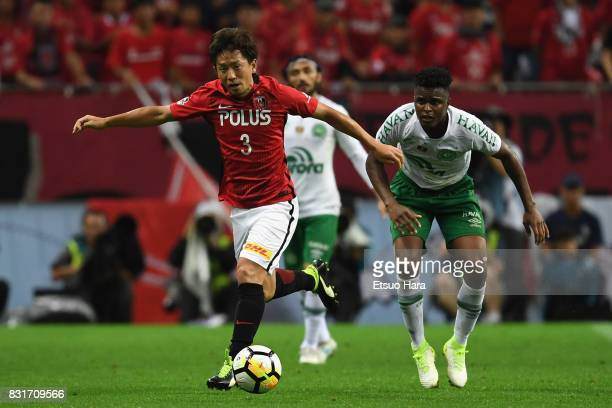 Tomoya Ugajin of Urawa Red Diamonds runs past Moises Ribeiro of Chapecoense during the Suruga Bank Championship match between Urawa Red Diamonds and...