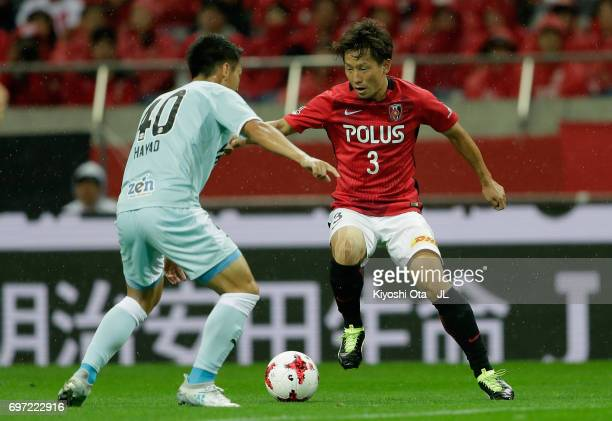 Tomoya Ugajin of Urawa Red Diamonds takes on Hayao Kawabe of Jubilo Iwata during the JLeague J1 match between Urawa Red Diamonds and Jubilo Iwata at...