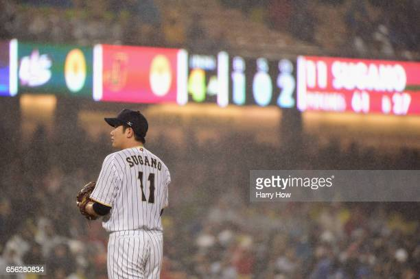 Tomoyuki Sugano of team Japan looks on in the rain during the fourth inning against team United States during Game 2 of the Championship Round of the...