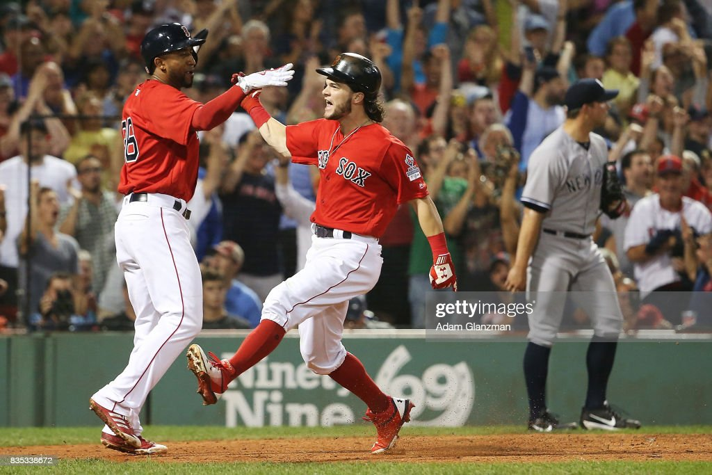 Tomy Kahnnle #48 of the New York Yankees looks on as Andrew Benintendi #16 and Eduardo Nunez #36 of the Boston Red Sox high five after scoring to take the lead in the seventh inning of a game at Fenway Park on August 18, 2017 in Boston, Massachusetts.