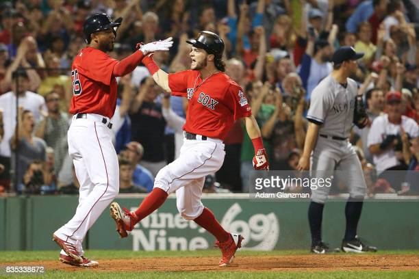 Tomy Kahnnle of the New York Yankees looks on as Andrew Benintendi and Eduardo Nunez of the Boston Red Sox high five after scoring to take the lead...